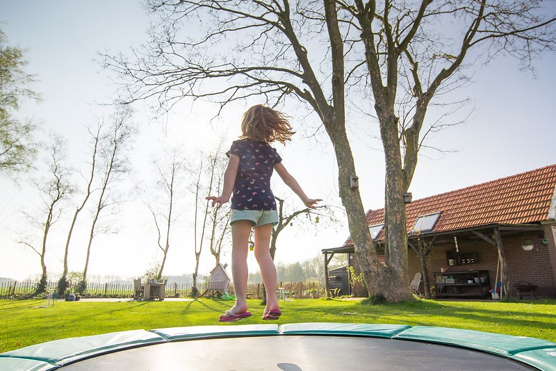 girl jumping on outdoor trampoline in the sunshine