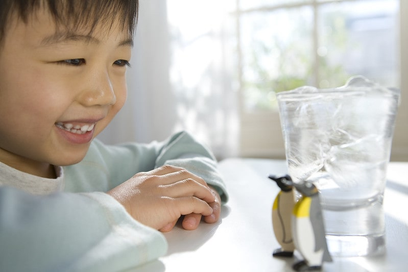 Boy sat at a table smiling at two toy penguins standing next to a glass of ice.