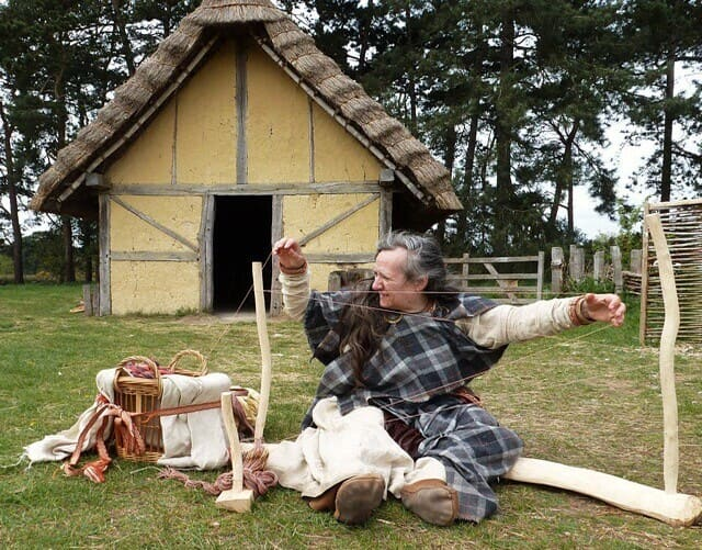 Woman dressed in Anglo-Saxon clothing, in an Anglo-Saxon village, sat on the floor weaving.