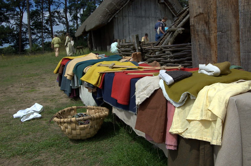 Anglo-Saxon style clothing laid out on a table in front of the huts in the Anglo-Saxon village.