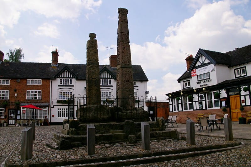 Town square in England with a pub in the corner and an Anglo-Saxon statue in the centre.