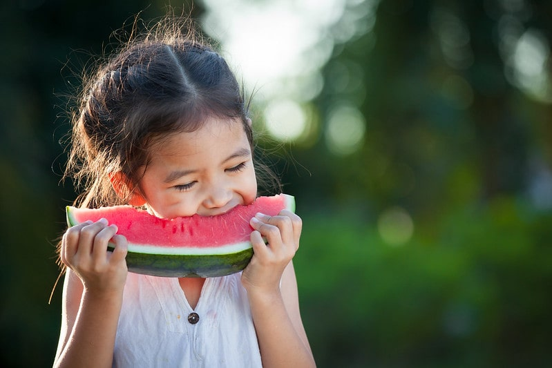 Girl biting into a wedge of watermelon, standing in the garden.