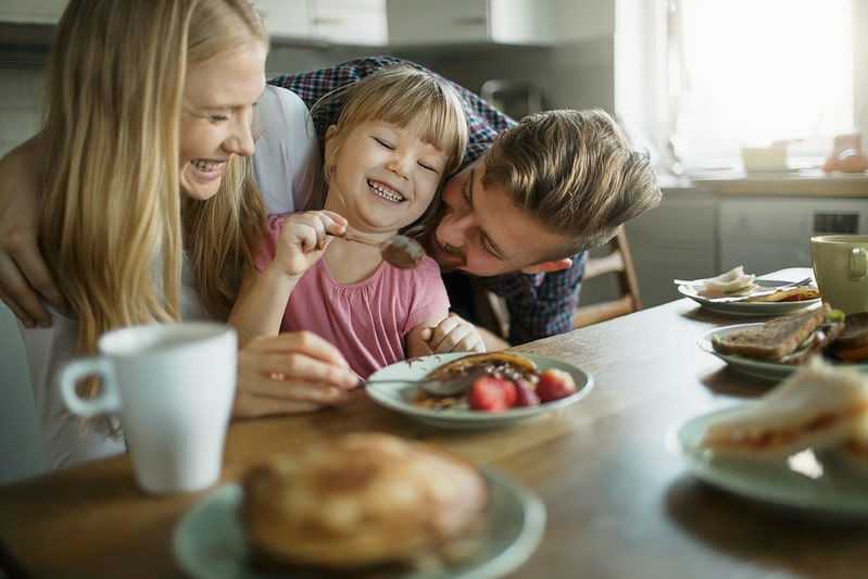 Happy family sat at the breakfast table laughing as they eat pancakes.