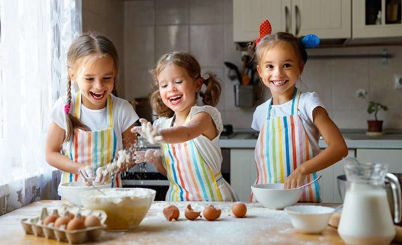 Three little girls in the kitchen smiling and laughing as they make pancakes.