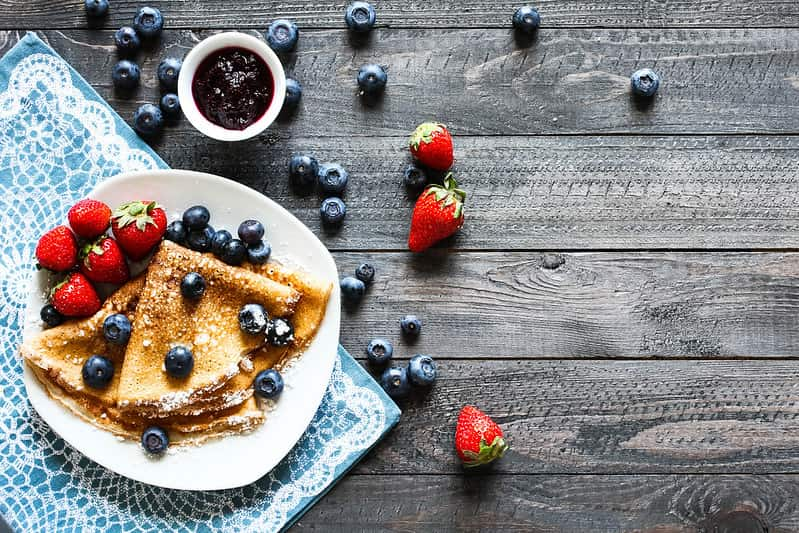 Plate of yummy folded crepes served with strawberries, blueberries and fruit compote.