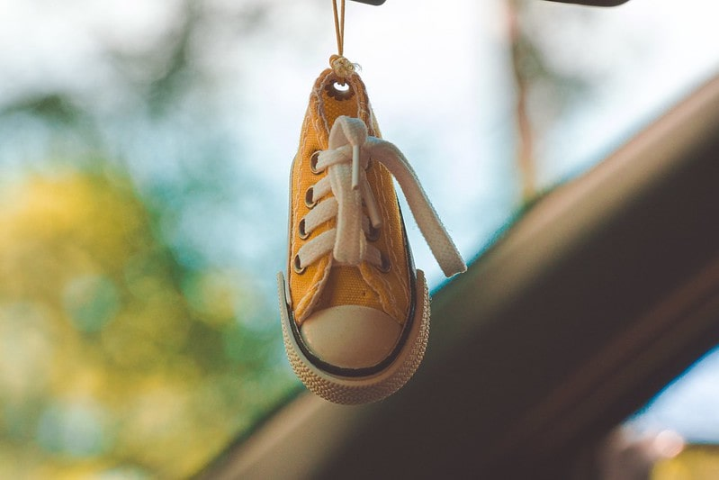 Yellow baby converse shoes hanging from car rearview mirror.