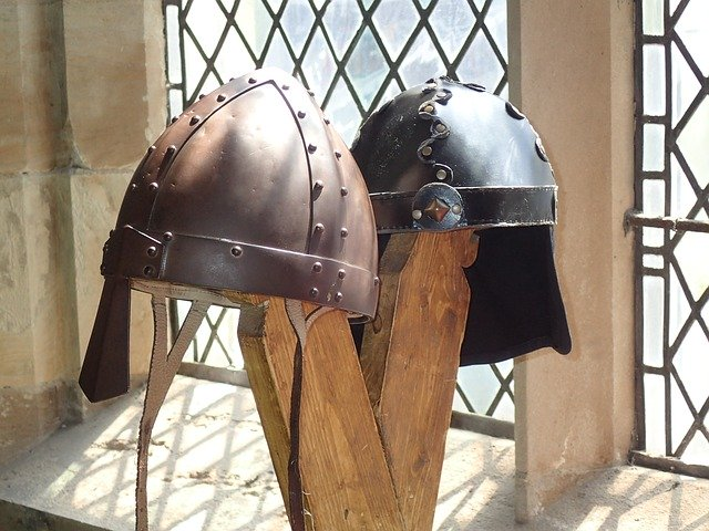 Two Iron Age helmets on a stand next to a window in a castle.