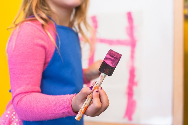 Girl holding a sponge brush with pink paint on it ready to do some Viking arts and crafts.