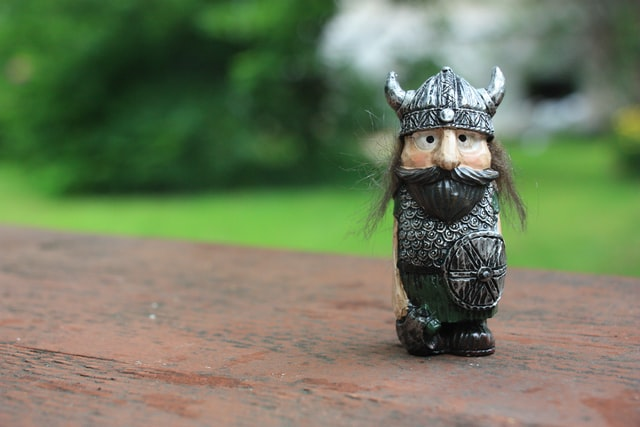 Toy of a miniature Viking man, with a typical Viking helmet carved, on a table.