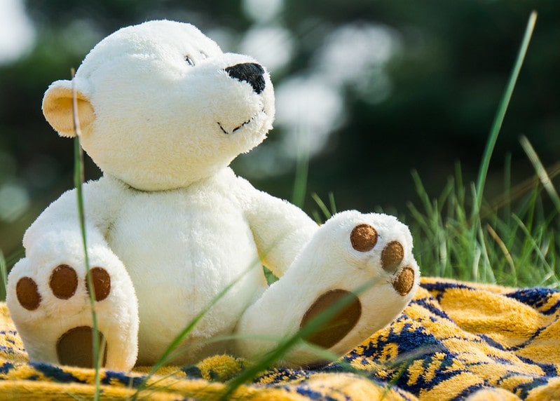 White teddy bear sat outside on a yellow picnic blanket.