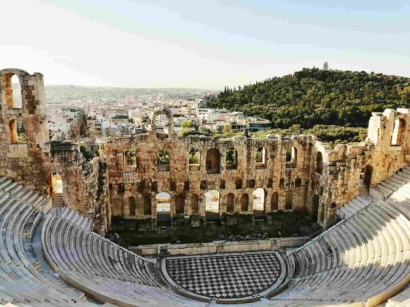 Ancient Greek amphitheatre with a view over the city and a hill.