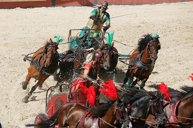 A Roman chariot race, two chariot drivers are close to each other.