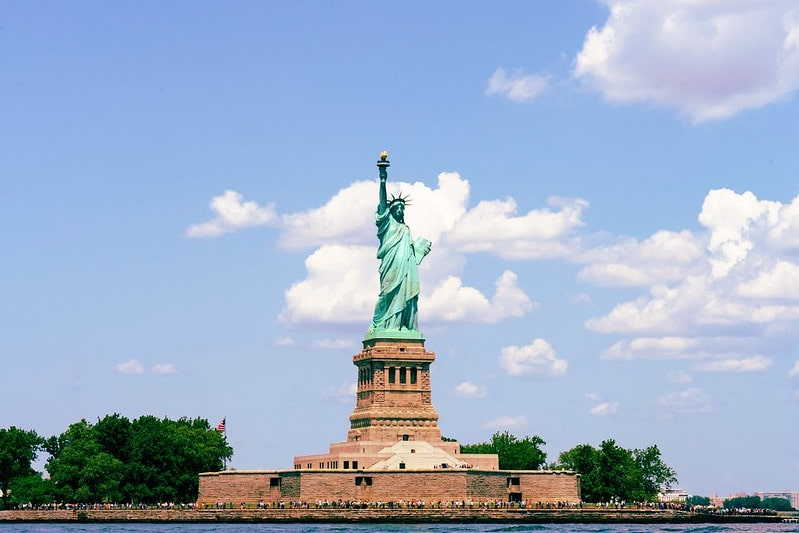 The Statue of Liberty on a bright day with blue skies and a few clouds.