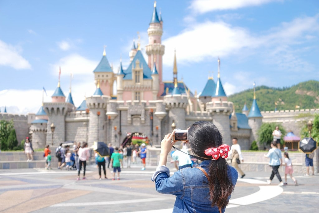 Girl wearing a Minnie Mouse scrunchie standing in front of the Disney castle taking a photo of it.