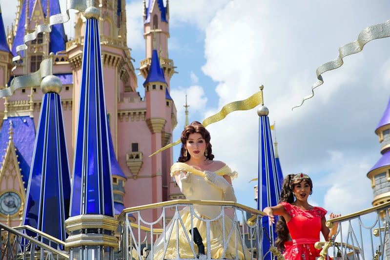 Princess Belle, from 'Beauty and the Beast', standing in front of the Disney castle.