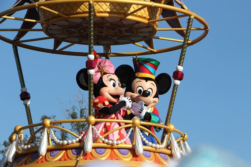 Mickey and Minnie Mouse standing on a parade float waving.