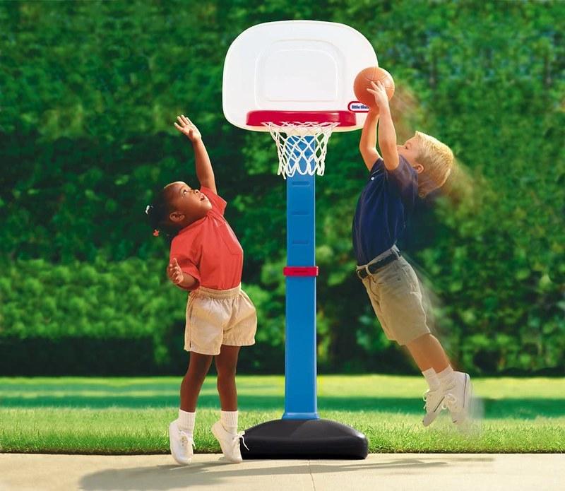 Two children doing a slam dunk in a children's basketball hoop.