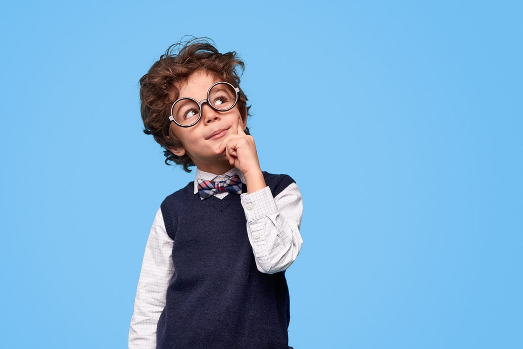 Smart-looking boy dressed in a shirt, sweater vest and bow tie and wearing glasses, thinks of corny riddles.