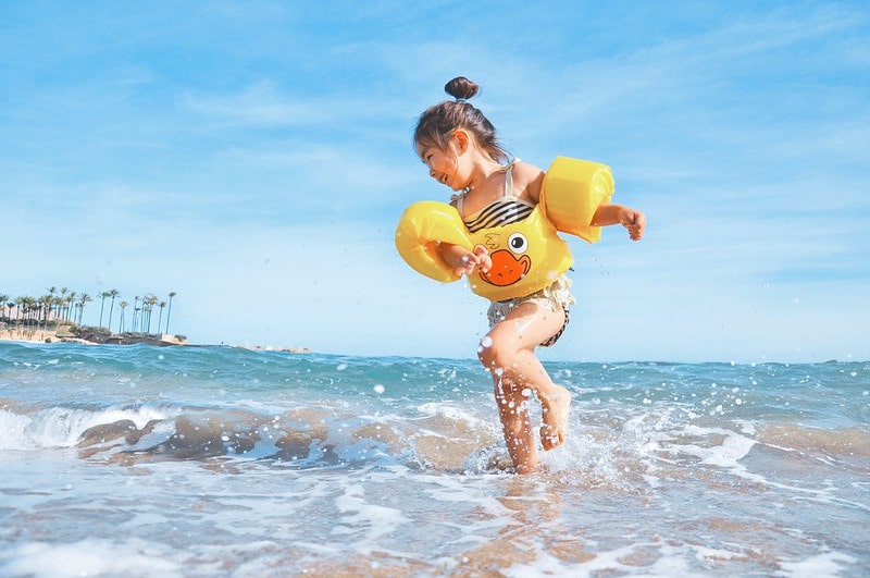 Girl splashing around in the sea at the beach wearing armbands and a floaty with a duck on it.