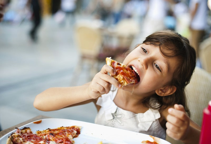 Young girl sat at the table in a restaurant eating a slice of pizza.