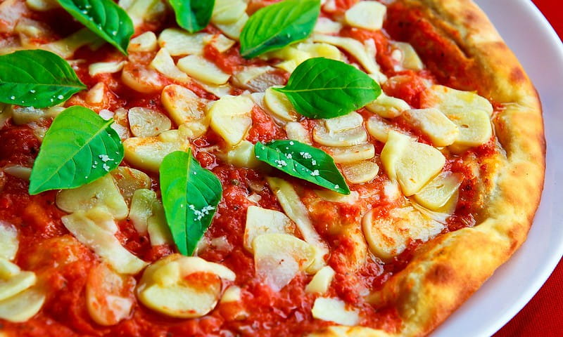 Vibrant looking pizza with garlic on top and basil leaves.
