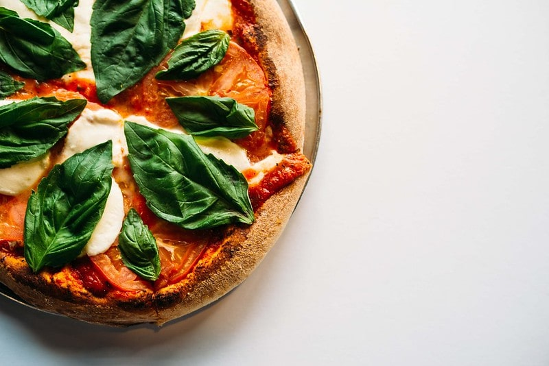 Homemade margarita pizza with big basil leaves on top.