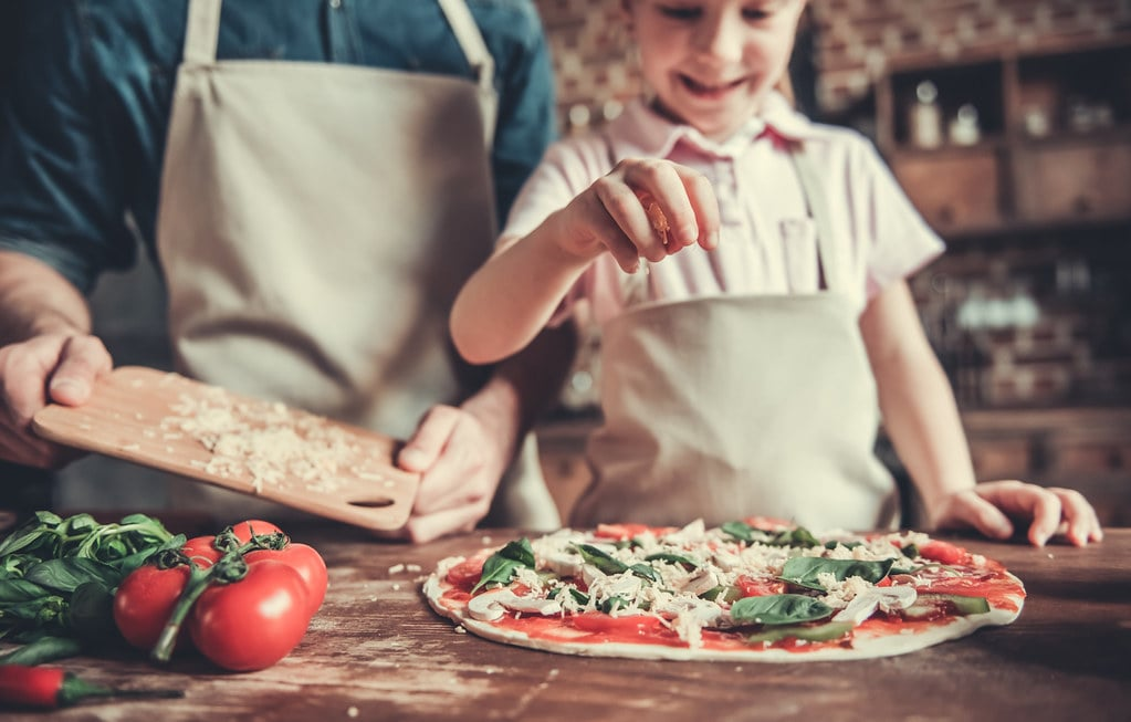 Dad and daughter in the kitchen making homemade pizza together.