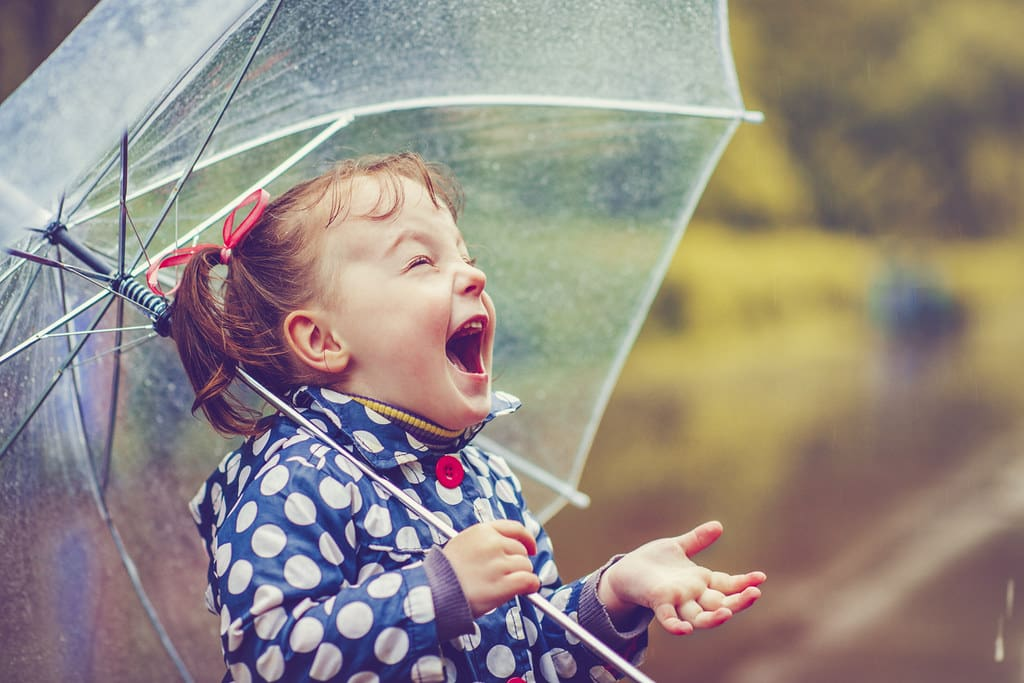 Little girl holding an umbrella laughing in the rain.