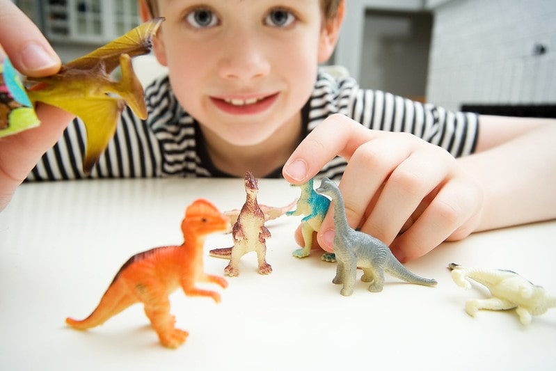 Young boy sat at the table playing with little toy dinosaurs.