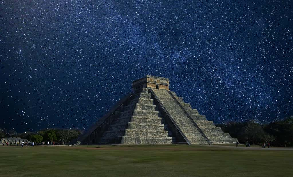 Chichen Itza at night with an amazing star-filled sky behind.