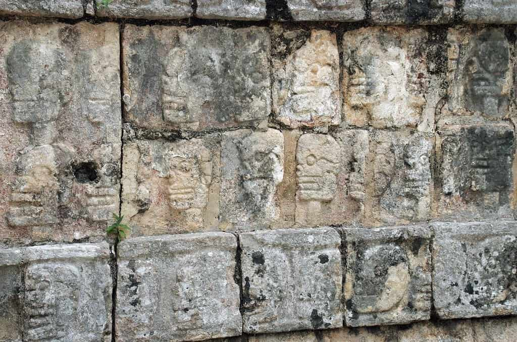 Old wall at Chichen Itza with faces engraved in the stone bricks.