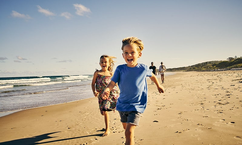 Kids laughing as they run along the beach.