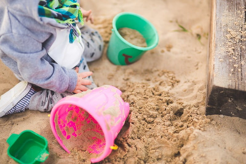 Toddler in the sand at the beach filling up buckets to make a sandcastle.