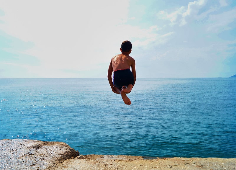 Young boy jumping into the sea.