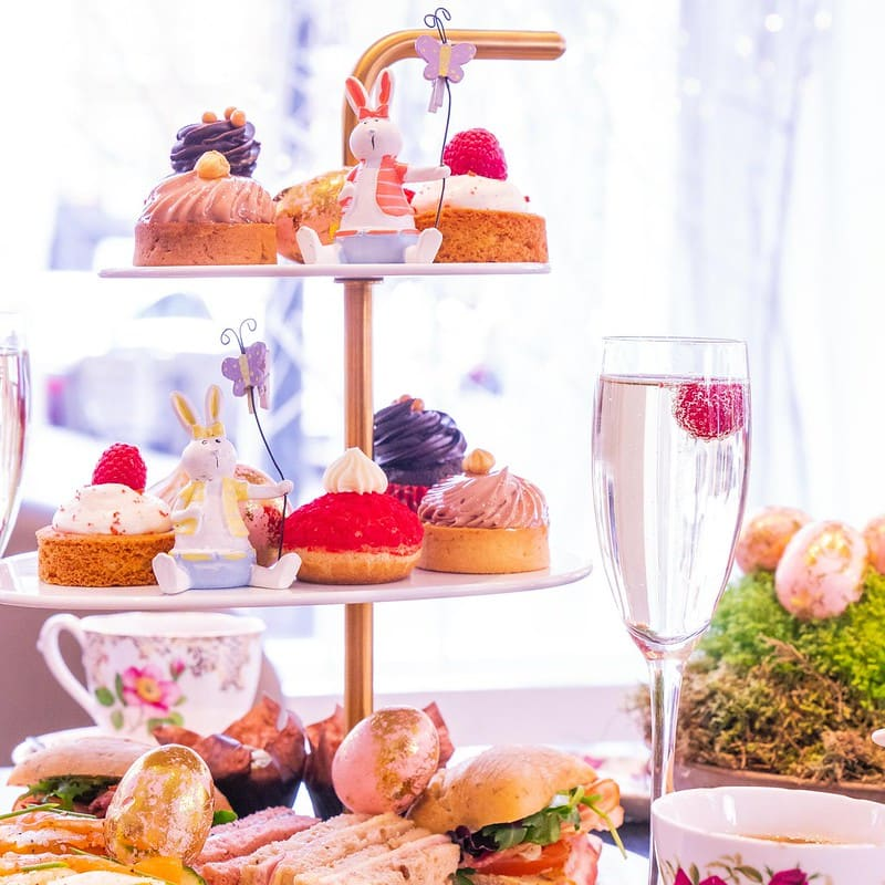 Afternoon tea on a cake stand including a glass of prosecco.