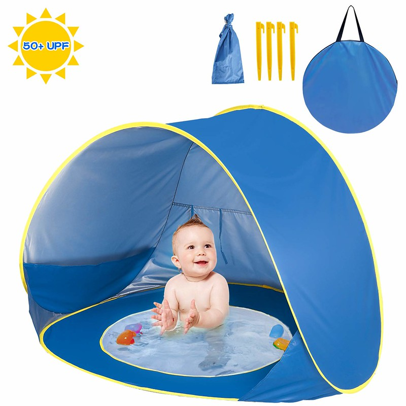 A baby paddling in the Shayson Pop Up Beach Tent.