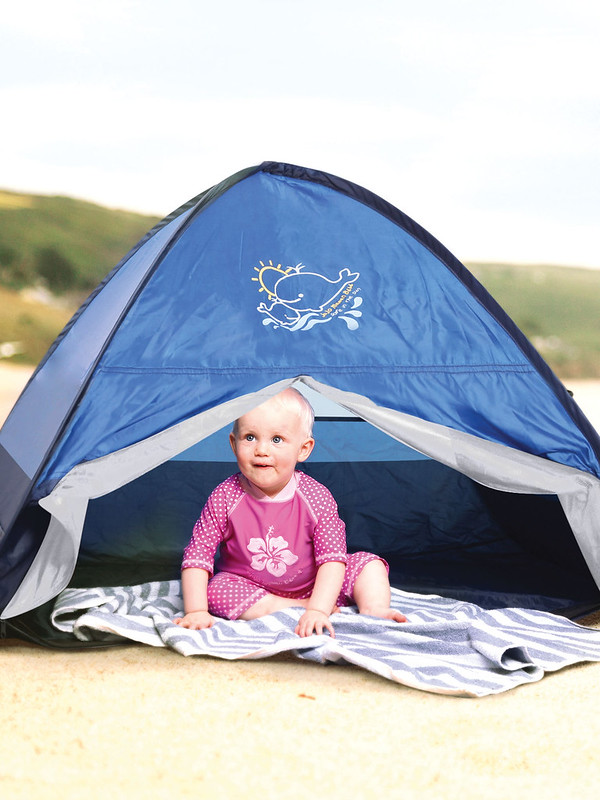Baby sitting in an Infant Sun Protection Tent.