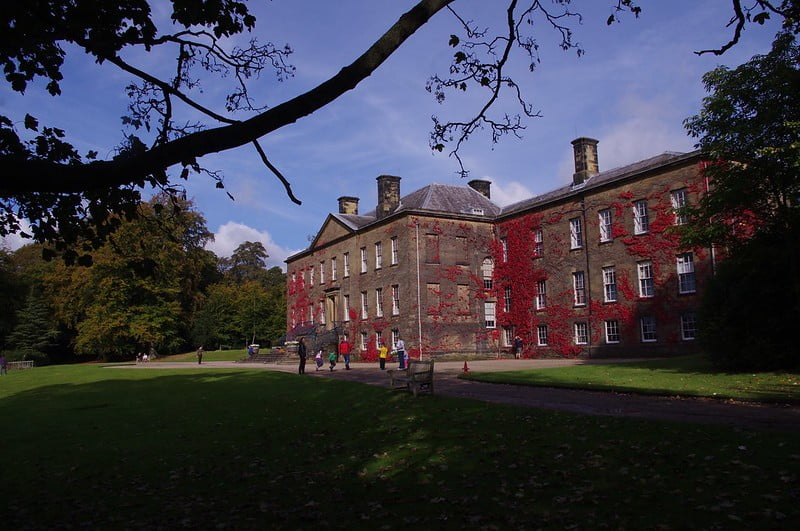 The historic Erddig House with surrounding trees and visitors admiring the facade.