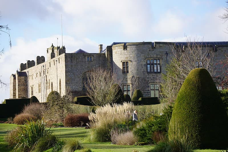 View of Chirk Castle from the gardens with a variety of green plants and hedges.
