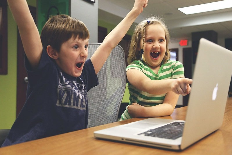 Young boy and girl looking at the computer laughing and cheering.