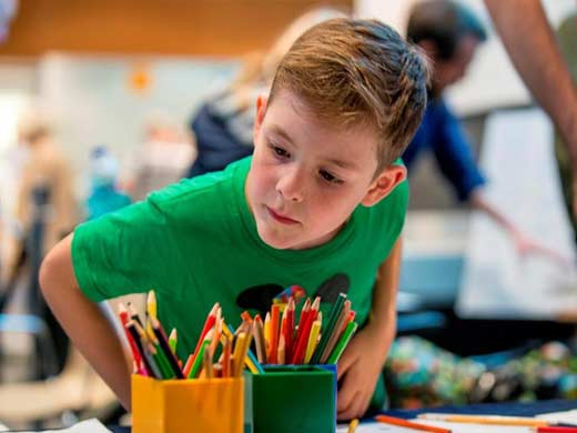 Young boy wearing a green t shirt choosing from two pots of coloured pencils.