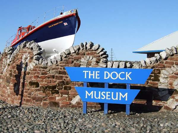 Entrance to the Dock Museum, Cumbria. There is a boat seemingly docked by the wall.