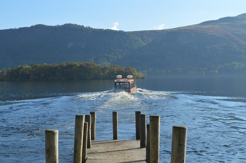 A boat moving away from the jetty on Windermere Lake overlooking the hills.