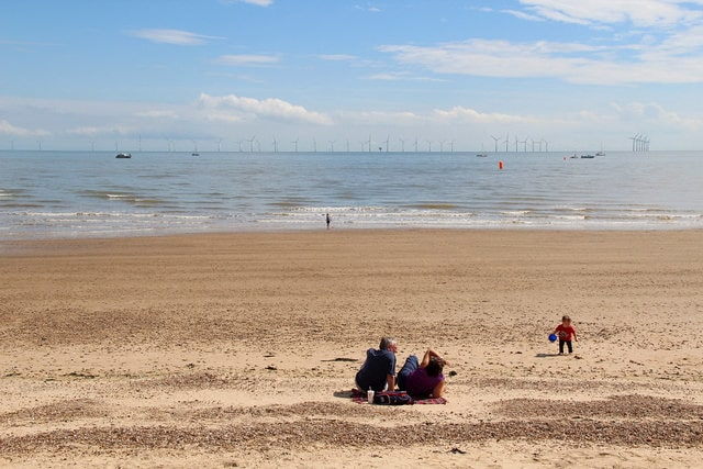 Family sat on the beach on a sunny day at Clacton-on-Sea.