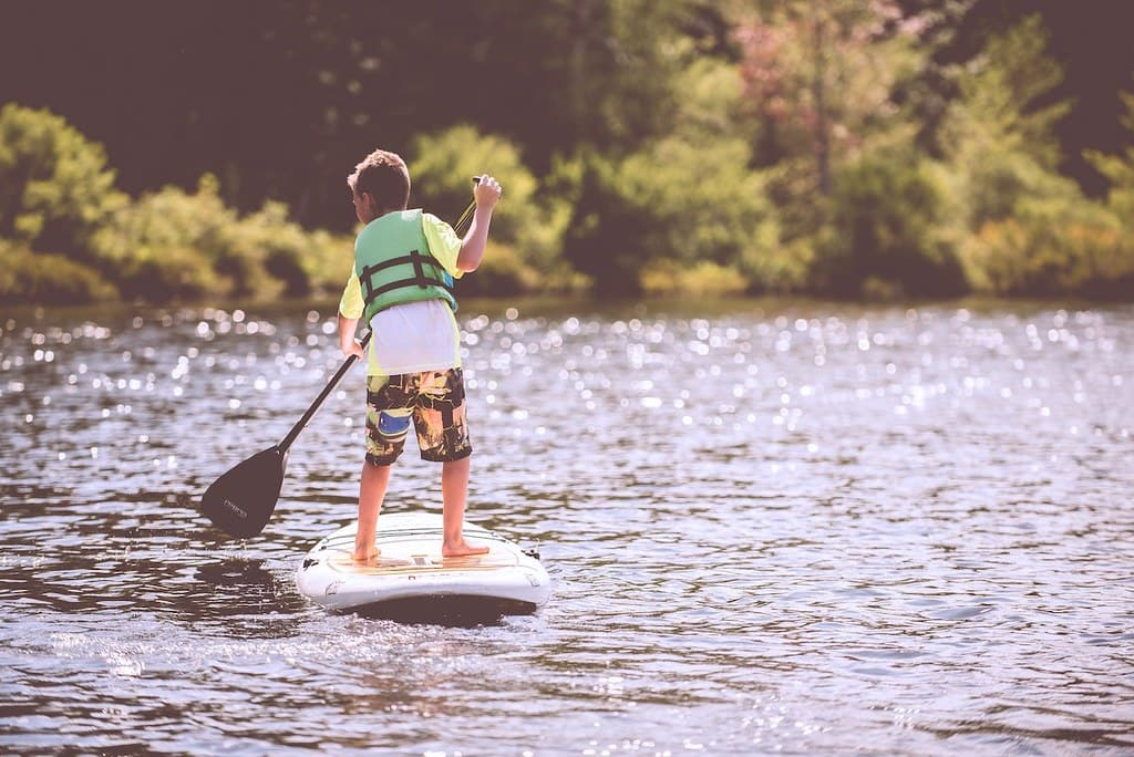 Young boy paddle boarding on a lake surrounded by trees.