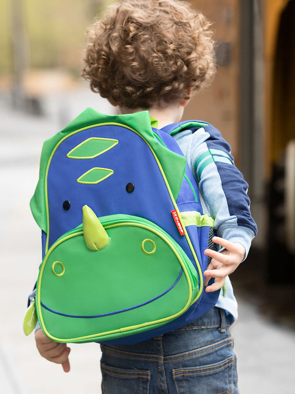 Child wearing the Skip Hop Zoo Pack Dragon Bag.