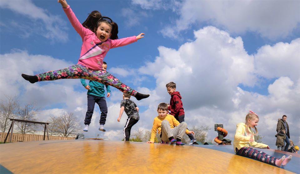 Kids jumping for joy and playing on a day out in Cardiff.