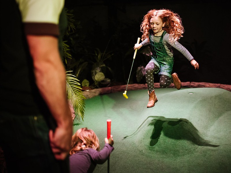 Little girl leaping over the adventure golf course holding a golf club.