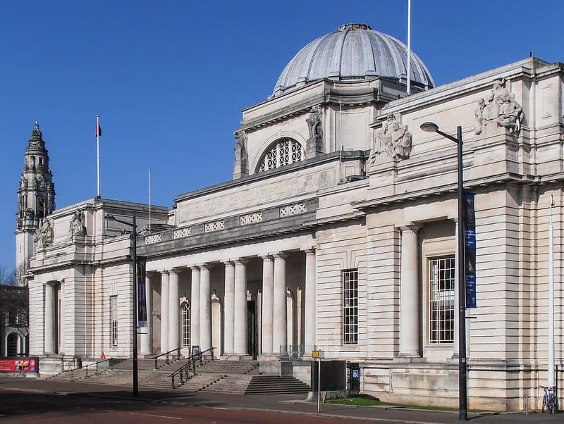 The grand front entrance to the Cardiff National Museum with statues and columns.