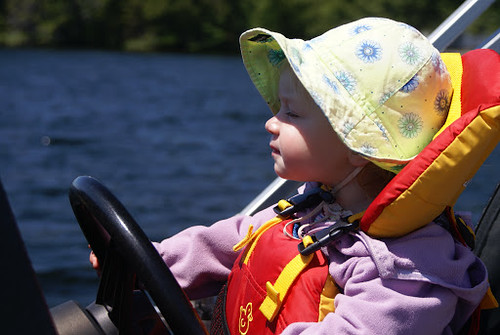 Baby sitting in a boat in a Salus Bijoux Baby Vest.